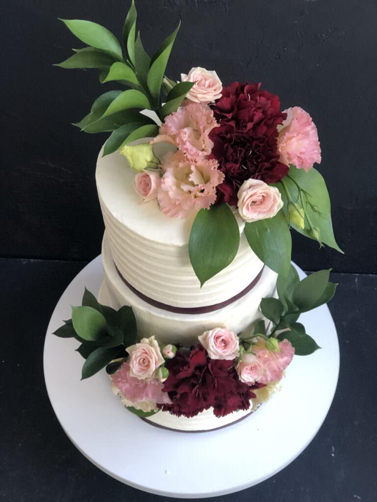 Свадебный торт с бордовыми лентами и живыми цветами